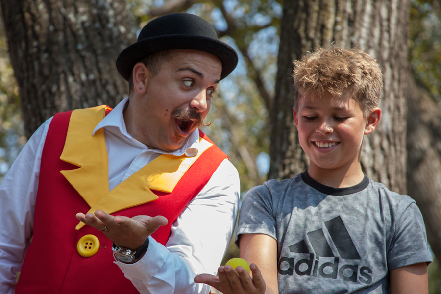 a boy performing a magic trick with Stevie in a Wow Factory community event show